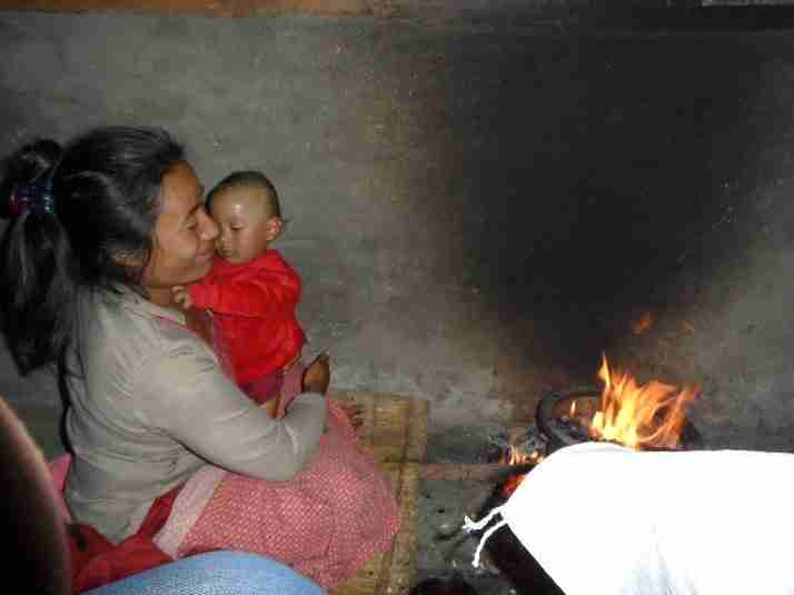 Cooking stoves Mother with baby by open fire